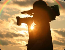 silhouette of film maker against golden sky and sun with clouds and rainbow