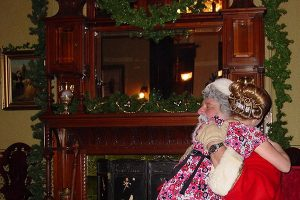 Girl in pink flowered dress hugging Santa while sitting on his lap, Victorian fireplace draped with Christmas greens behind