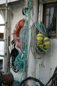 Yellow & blue bouys, ropes, red life preserver ring hanging on white wall of commercial fishing boat