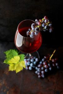 glass of red wine, bunches of purple grapes draped over glass and at bottom with leaves - Roberta Sorge on UnSplash