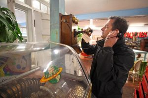 Man making call on antique brown telephone, glass display case in front at Vintage Hardware. Don Frank Photography