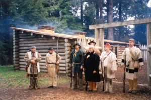 Fort Clatsop Park Rangers in brown period costumes standing in front of log building with green pine trees behind