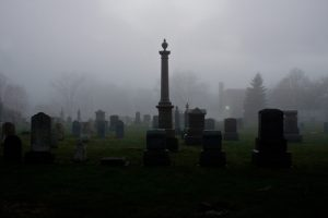Cemetery in foggy gray dusk with single tall monument and many lower headstones by Scott Rodgerson on UnSplash
