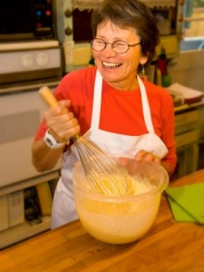 smiling female cook in red blouse and white apron mixing batter in glass bowl on wooden counter with large whisk