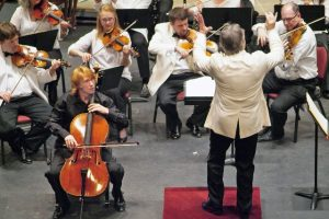 Conductor standing on red podium conducting strings section wearing white shirts, black pants, cello soloist in front dressed in black