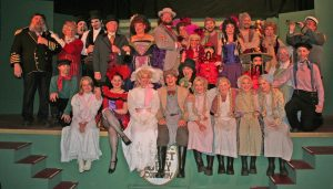 Shanghaied in Astoria cast - two rows of people in Victorian costume standing on and in front of green stage