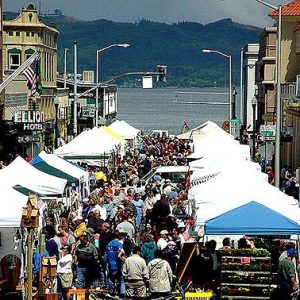 Crowded open-air street market bordered by Victorian buildings with Columbia River and hills on far shore in background