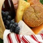 Picnic basket with red and white striped cloth, grapes, round bread, yellow cheese