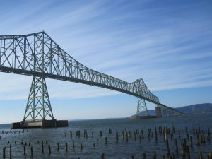 silhouette of Astoria-Megler Bridge over blue water of Columbia River, pilings in water in foreground