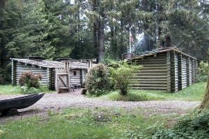 Entrance to Fort Clatsop with log fort buildings and green trees behind - National Park Service