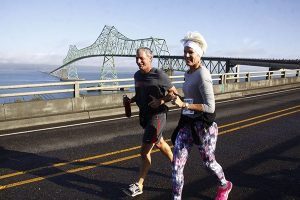 Older man in dark running clothes & woman with white headband. flowered pants running on road, Astoria-Megler Bridge behind