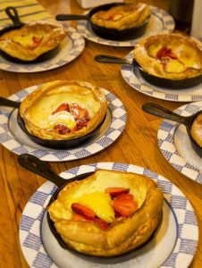 Inidividual iron skillets with dutch pancake topped with strawberries; skillets on blue & white check plates