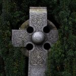 Closeup of gray Celtic cross tombstone with greenery background by Adrian Moran on UnSplash