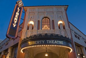 Looking up at Liberty Theatre facade with windows and round marquee. White lights on name and marquee