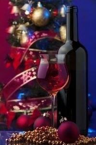 glass of red wine, dark wine bottle in front of glass cylinder of Christmas balls and ribbons, gold beads