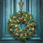 Holiday wreath with red and yellow fruit decorations on blue-green paneled door with by Jez Timms on UnSplash