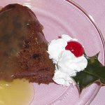plum pudding with sauce & garnish of whipped cream, cherry, holly on glass plate on pink tablecloth