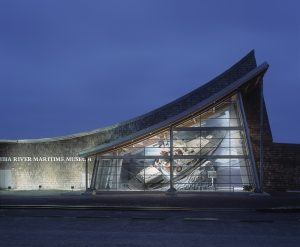Lighted glass and gray stone triangular facade of Columbia River Maritime Museum at night