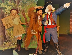 Actors on stage - Cowgirl holding book, Lewis & Clark in buckskin and blue army costumes looking and pointing away