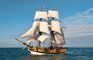 Two-masted Tall Ship Lady Washington with white sails under sail at sea by Bob Habison