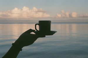 hand&arm holding coffee cup up against view of ocean