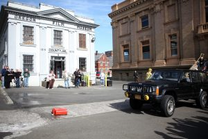 Oregon Film Museum white facade, people in front & black vehicle on right reenacting The Goonies film