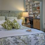 queen bed with green & white print bedspread, table lamp, bookshelves on right