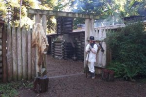 Park Ranger in period costume standing by entrance to log Fort Clatsop