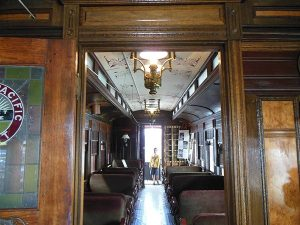Door to 1888 railroad coach with seats, hanging lights, boy standing at end of car