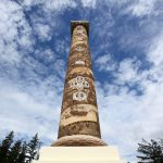 sgraffito frieze on Astoria Column with blue sky and clouds in background