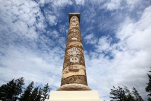 view looking up at Astoria Column's sgraffito frieze with blue sky, clouds, evergreen tops in background by Don Frank