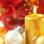one white and one gold Christmas tree balls leaning against lighted gold cylinder candle, red petals in background