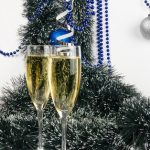 two glasses of champagne with frosty evergreens in background