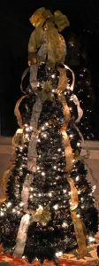 tall narrow Christmas Tree with gold vertical ribbons and white lights in front of window at night