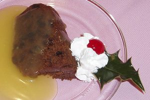 plum pudding, lemon sauce on glass plate with whipped cream, cherry, holly garnish, set on pink tablecloth