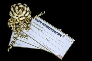 stack of three gold-edged white gift certificates decorated with elaborate gold ribbon bow, black background