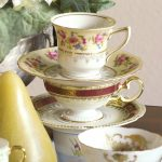 stack of fine china tea cups and saucers with gold napkin on left and white flowers in background