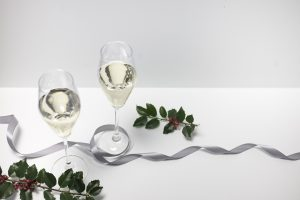 two glasses of champagne on white cloth with holly sprigs