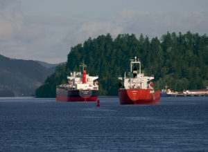 two white and red ships on water evergreen forested mountains in background by Michelle Roth Photography