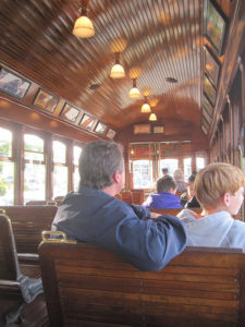 backs of man in blue jacket and boy sitting on wooden seat inside 1913 trolley with curved wood paneled ceiling