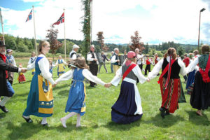 ring dancers in Scandinavian costumes on green lawn at Astoria Oregon  Midsummer Festival