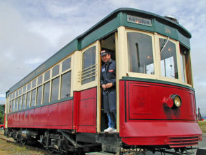 Red, cream and green Astoria Riverfront Trolley on tracks with conductor in open doorway