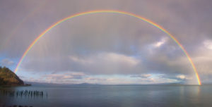 full rainbow arching over Columbia River at Astoria - hills on left, gray and white clouds against blue sky