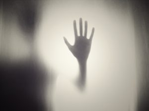 gray silhouette of hand held up with fingers spread surrounded by whitish fog