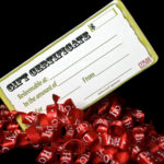 Christmas gift certificate with red curling ribbons against black background