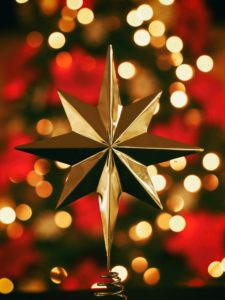 gold star against out of focus red pointsettias and white lights