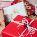 pile of holiday gift packages wrapped in red white and brown paper with ribbons
