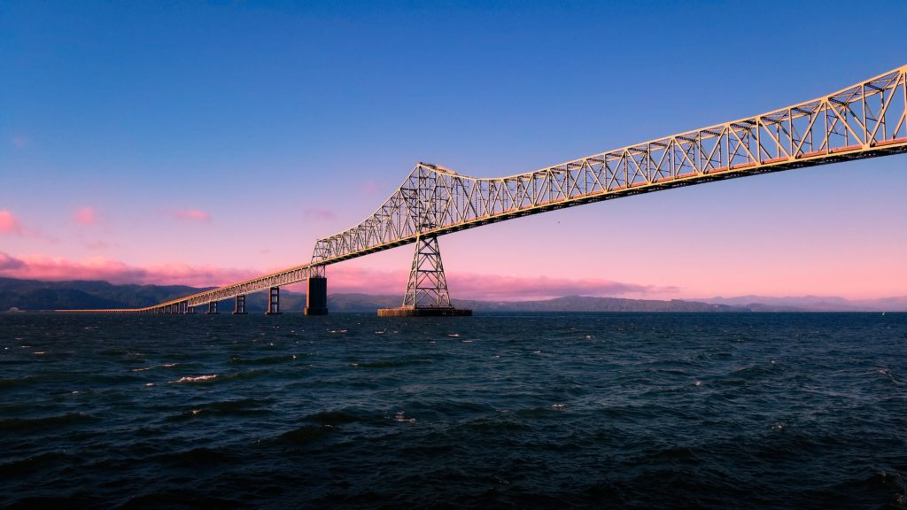 The Astoria-Megler Bridge crossing the Columbia River under a blue and pink sky.