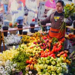 A beautiful stand at a farmers market with beautiful bouquets of yellow, red, and green flowers