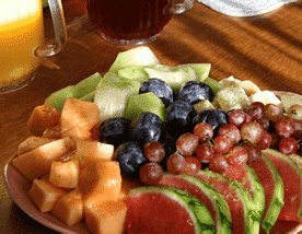 Plate packed with fresh fruit - watermelon, canteloupe, honeydew, and grapes on a table with juice.